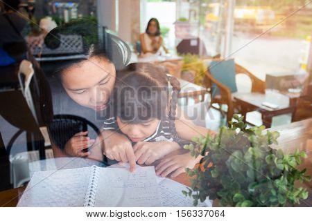 happy family mother and daughter read a book at cafe