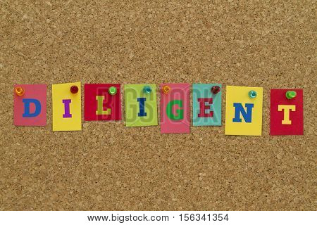 Diligent word written on colorful sticky notes pinned on cork board.