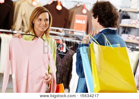 Portrait of pretty woman holding tanktop while asking her boyfriend for advice