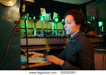 Woman works with computer near laser educational installing in lab