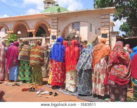 Mujer africana orando con tejidos colores, Camerún, África