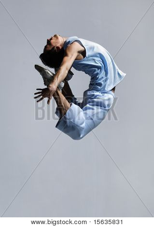 stylish modern ballet dancer jumping on grey