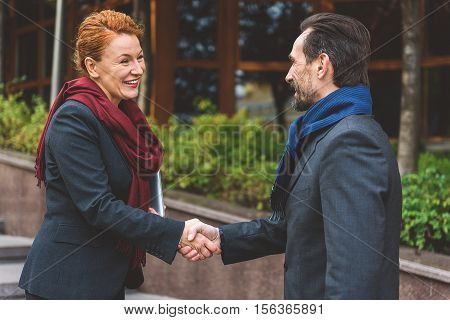 Joyful businessman and woman are getting acquaintance while standing outdoors. They are shaking hands and smiling
