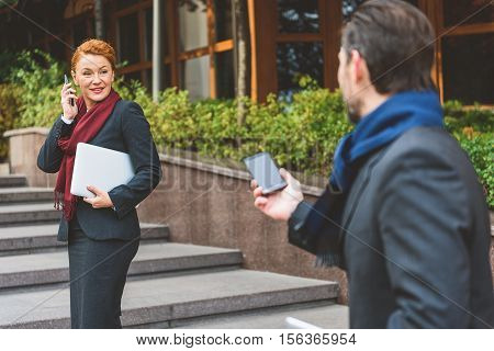 First acquaintance. Business partners are meeting on street. They are holding phones and looking at each other with surprise. Woman is standing and smiling