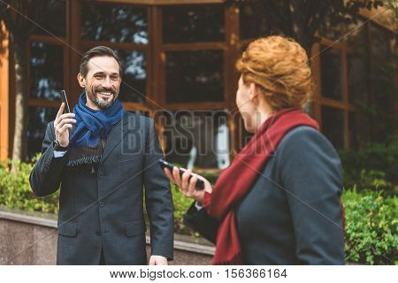 Happy colleagues are meeting on street. They are looking at each other with surprise and smiling. Man and woman are using phones