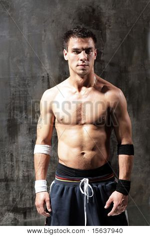 young fighter man posing on grunge background