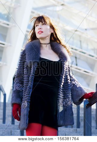 Sexy woman in a black dress red tights and a fur coat standing on stairs