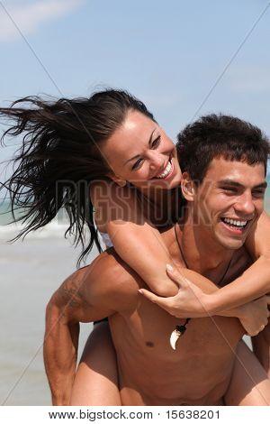 running beautiful couple on the sandy sea beach