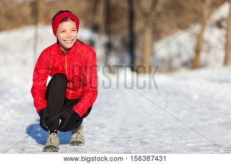 Running athlete woman getting ready for outdoor run tying up running shoes laces during winter season. Outside cardio training in cold snow weather. Asian girl wearing gloves, headband and jacket.