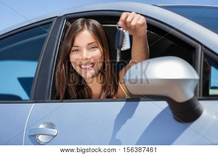 Driving new rental car or drivers license concept. Young teenager woman driver holding car key driving her new car. Beautiful multiracial Asian woman smiling showing new car keys.