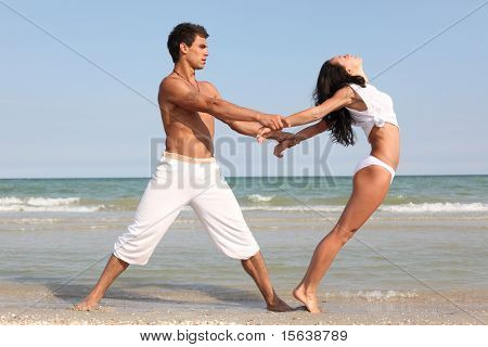 young beautiful couple posing on sea shore