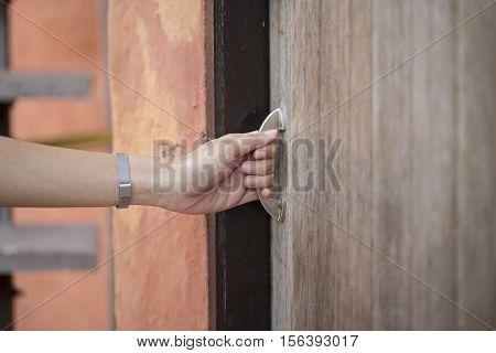 hand hold handle of wood door, close up
