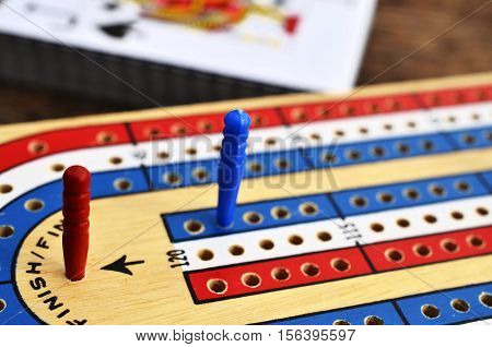 A low angle image of a wooden cribbage board with the red cribbage peg in the winning position and the jack of spades in the background.