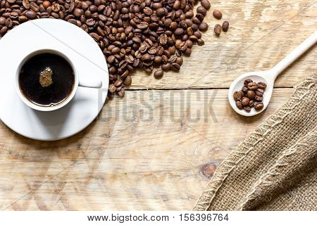 cup of coffee, beans and spoon on wooden background top view