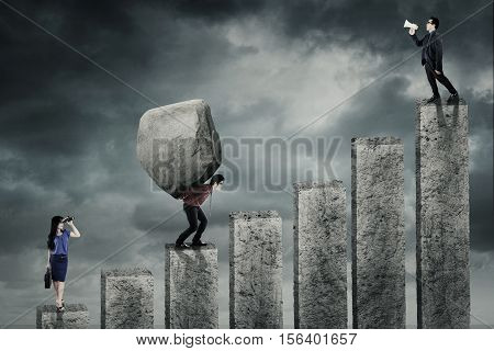 Businessman shouting his employee using megaphone and businesswoman looking through binocular while her partner lifting burden on the graph