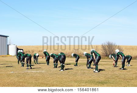 A team of high school football players in green and black jerseys doing stretches before a game in autumn
