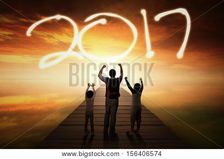 Portrait of father and his kids raising hand and standing on the wooden bridge while looking at numbers 2017 on the sky