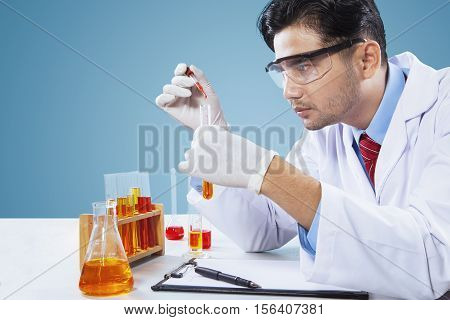 Portrait of male scientist makes chemical research by using chemical liquid in laboratory