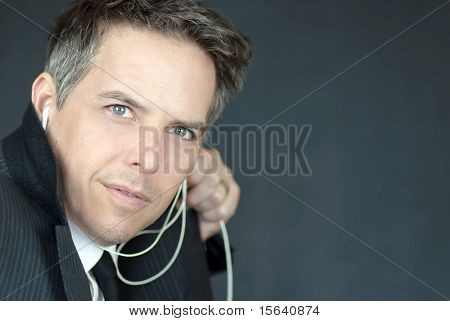 Confident Businessman Wearing Headphones Looks Sideways To Camera