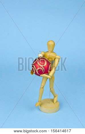 One wooden artist manikin with red christmas bauble on blue azure background