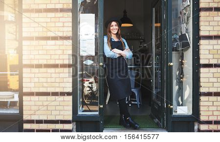 Beautiful young woman in apron and hat leaning against doorway of brick wall coffee house or restaurant as owner or employee