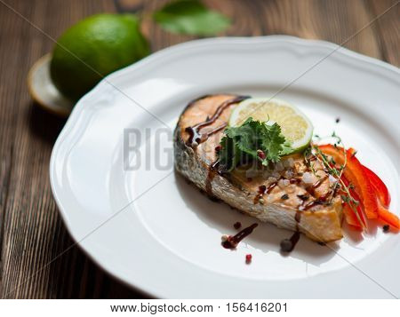 Baked red fish steak salmon on the white plate with vegetable garnish