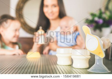 Bottle with milk and manual breast pump. Daughter holding baby bottle and helps to mother at background, kitchen. Mother's breast milk is the most healthy food for newborn baby. Happy family concept