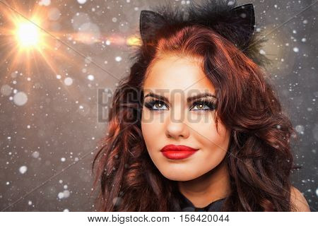 Beautiful woman with carnival cat mask looking at star, Christmas night. Cristmas party. Secret. Fashion. Venetian carnival. Hot babe. Party. Snow background
