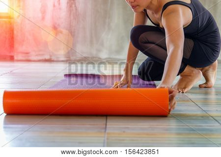 Woman rolling her mat before a yoga class