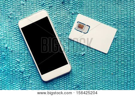 Smartphone with blank screen and mobile phone gsm SIM card on the table top view