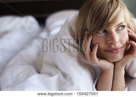 Beautiful woman lying in bed looking away
