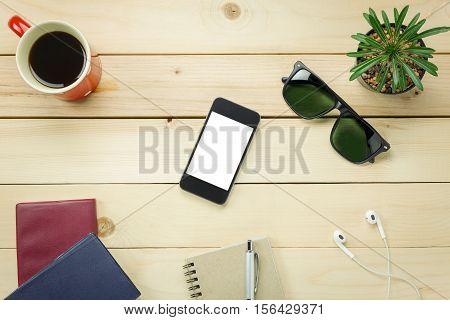 Top view notepaper pen cactus watch mobile phone paper clips Laptop earphones on office desk background.