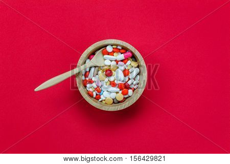 Top view colorful medicine and wood spoon bowl on red background.Take a medicine concept.
