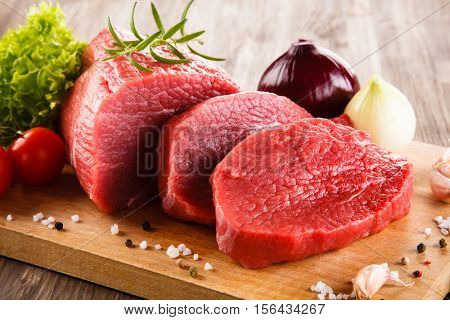 Fresh raw beef on cutting board and vegetables
