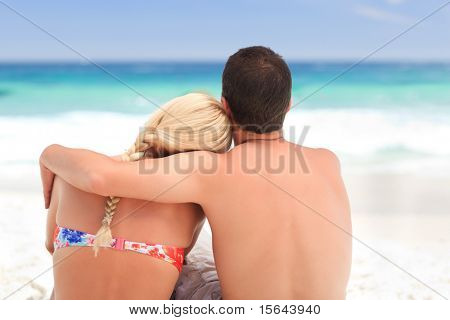 Man hugging his girlfriend while they are looking at the sea