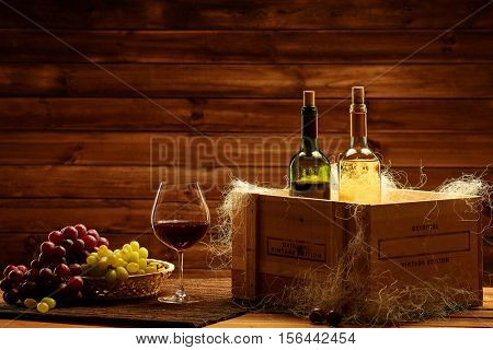 Bottles of red and white wine, glass and grape on a wooden interior.