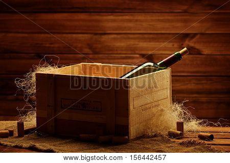 Bottle of wine in box in wooden interior.