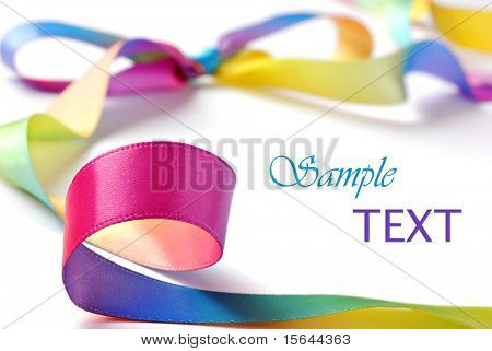 Shiny satin rainbow ribbon on white background with copy space.  Macro with extremely shallow dof.