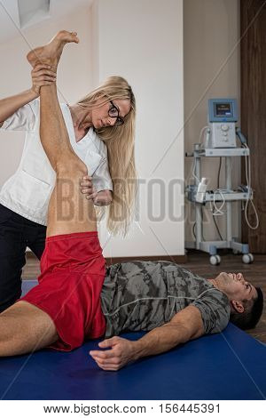 Physical therapist streching patient's legs, toned image