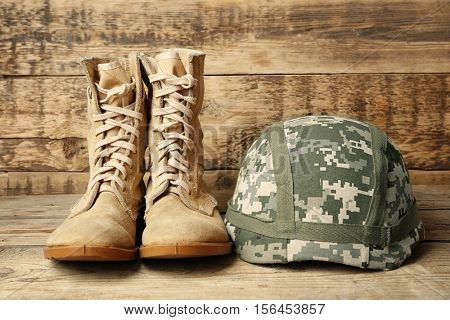 Pair of combat boots and military helmet on wooden background, close up