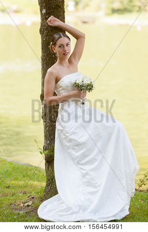 Beautiful bride in white with bridal bouquet in hand leaning relaxed on a tree by the lake