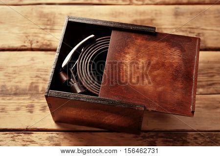 Stylish box with leather belt on wooden background