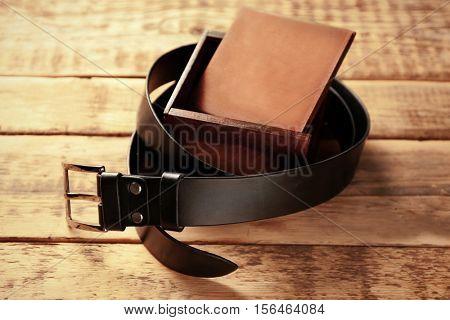 Stylish leather belt with box on wooden background