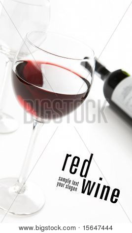 Glass of red whine. Bottle in background. Photo taken in angle.