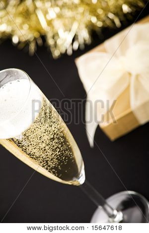 Glass of champagne, elegant golden gift box with white ribbon. All on matt black background.