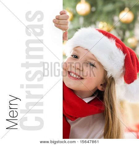 Beautiful young blonde girl in santa hat and red comforter behind white board. Space for text isolated on white.