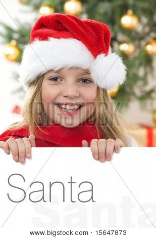 Pretty blond hair girl with santa hat and red comforter holding white board with space for text isolated on white. Christmas tree in background