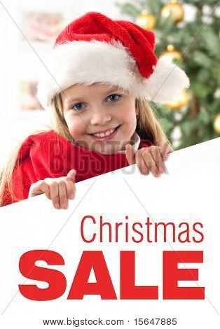 Menina de cabelos loiros muito com edredão de chapéu e vermelho de santa segurando uma placa branca com espaço para texto isol