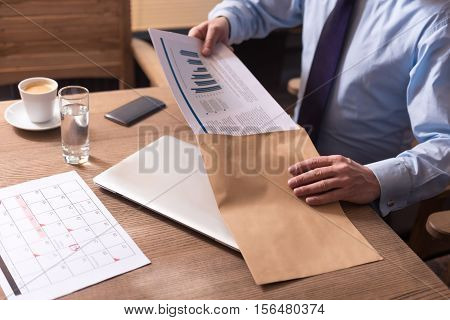 Prepared to be sent. Diligent hard working responsible man holding the documents and putting them into the envelope while sitting at the table