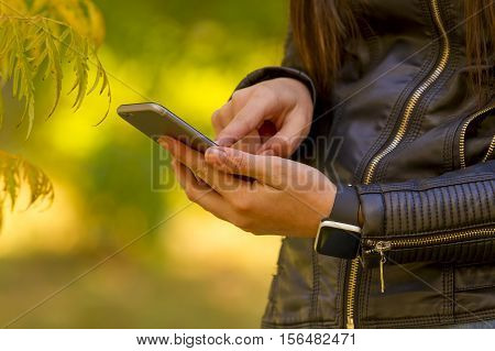 Young girl using smart phone in the park wears smart watch in everyday lifestyle. Focus on smart phone!